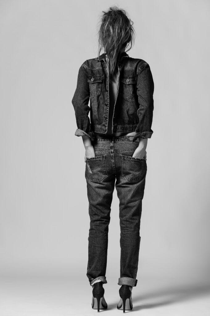 öppen jeansjacka i rygg med jeans och uppsatt hår
